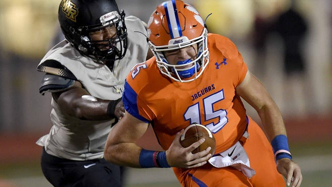 Madison Central quarterback Jack Walker (15) tries to beat a Northwest Rankin defender to the edge on Friday. Walker had two rushing touchdowns in the Jaguars' win over the Cougars.