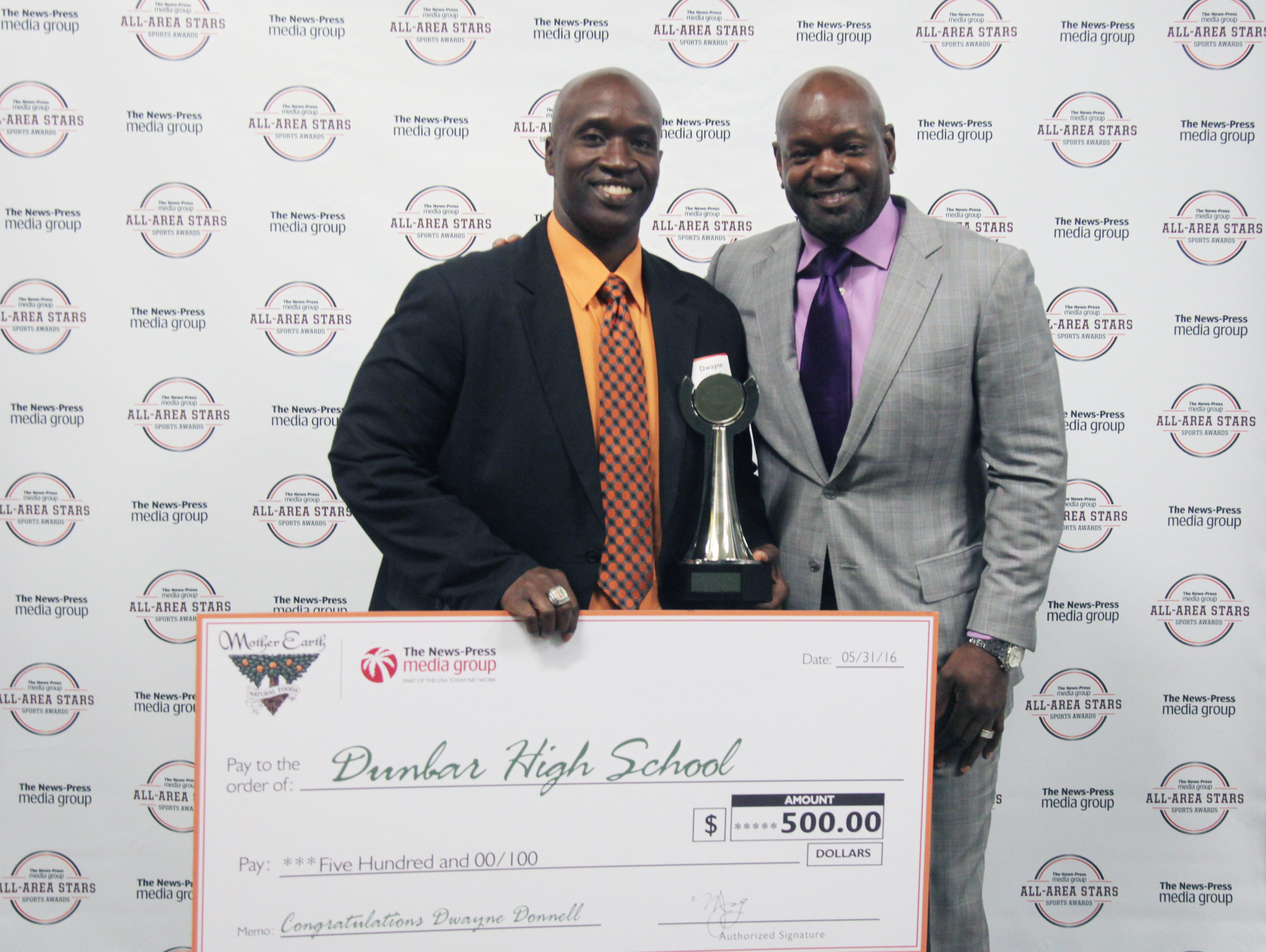 Dwayne Donnell, of Dunbar High School, poses with Emmitt Smith after being named Coach of the Year during the All-Area Stars Banquet at Germain Arena on Tuesday.