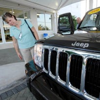 Car buying customer Debbie Bradley leans forward to look at the grille on a 2006 Jeep Commander at Arrigo Dodge-Chrysler-Jeep in West Palm Beach, Florida.