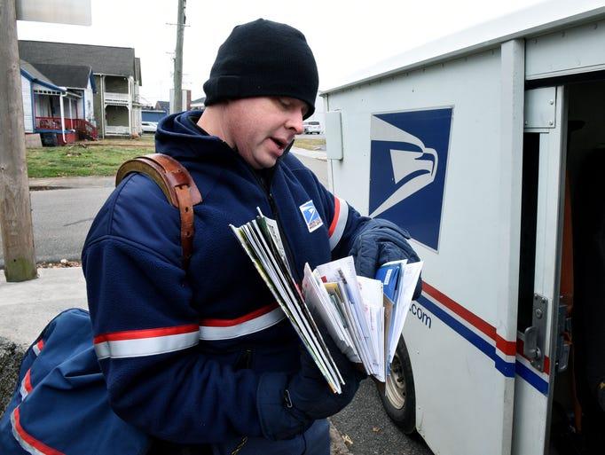 Postal carrier Jason Littlejohn checks mail for one