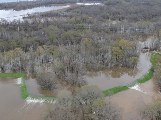 Water overflows the levee about four miles west of Bastrop on Saturday.