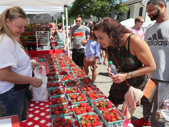 Donna Bornitz (left) of Schmit Farms in Mequon and East Troy sells strawberries to Madeline Gonzalez (center) of Milwaukee and Earl Jackson of Glendale (right) at the 2018 Cedarburg Strawberry Festival.