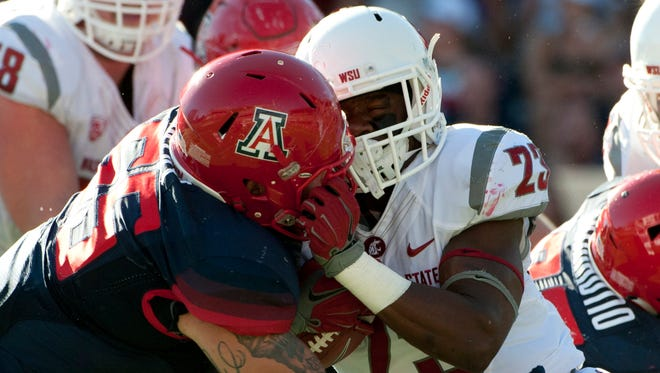 Oct. 24, 2015; Tucson; Washington State Cougars running back Gerard Wicks (right) is tackled by Arizona Wildcats defensive lineman Jeff Worthy (55) during the third quarter at Arizona Stadium. The Cougars won 45-42.