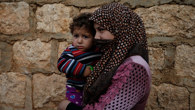 Holding a child, a woman waits to receive humanitarian aid distributed by the Red Crescent, in Mersewa village, in the greater Afrin district, Syria, during a Turkish government-organised media tour into northern Syria, Saturday, March 3, 2018.