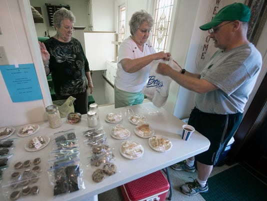 Greg Mollenkopf, right, buys chicken corn soup from Norma Metz. Trish Chaney is at left. A soup and sandwich sale at Cross Roads United Methodist Church at the polling place for the borough inside the church Tuesday May 19, 2015.