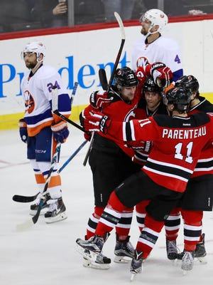 Islanders players Stephen Gionta, top left, and Dennis Seidenberg, top, skate by as Devils players, from left, Pavel Zacha, Adam Henrique, PA Parenteau and Joseph Blandisi celebrate a goal by Zacha during the third period of the game Saturday, Feb. 18, 2017, in Newark.