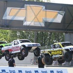 Drivers Robby Gordon, left, Arie Luyendyk Jr., center, and Apdaly Lopez take a jump during the SPEED Energy Stadium SUPER Truck Series auto race in Detroit, Friday, May 30, 2014.