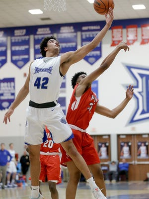 Hamilton Southeastern's Zach Gunn (42) pulls in a rebound over Pike's Darian Porch (32) in the first half of their game Tuesday, February 14, 2017, evening at Hamilton Southeastern High School