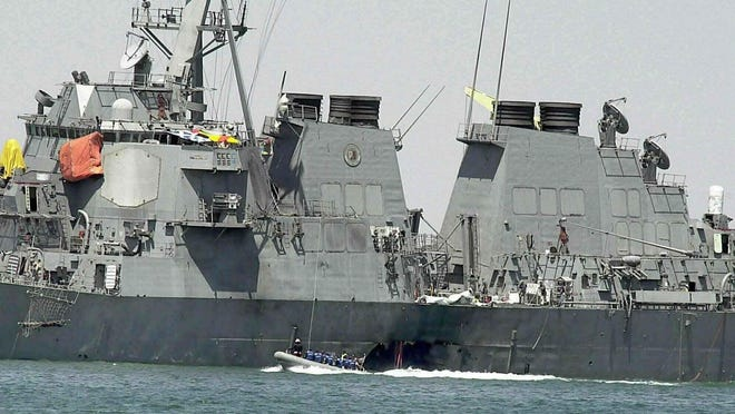 Experts in a speed boat examine the damaged hull of the USS Cole at the Yemeni port of Aden after an al-Qaida attack that killed 17 sailors on Oct. 15, 2000. Sudan's transitional government said Friday it's reached a settlement with families of the victims of the 2000 attack on USS Cole in Yemen, in a bid to have the African country taken off the U.S. terrorism list.