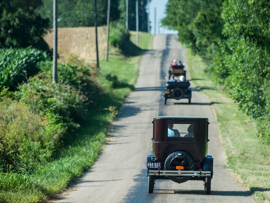 A line of Model Ts travel down a rural road in western