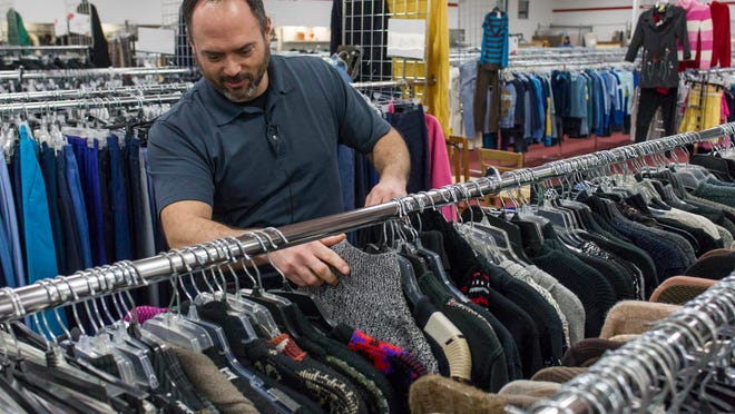 J.J. Ramon hunts through the clothing rack at Salvation Army for possible ugly sweaters.