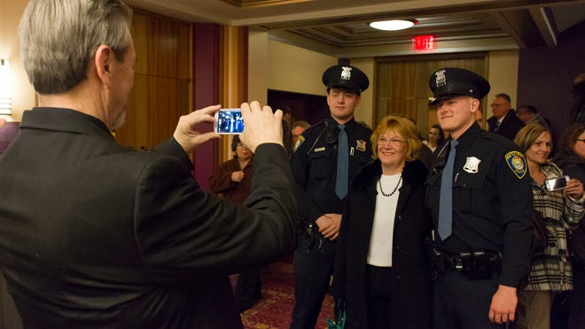 Lee Davis composes a photograph of his wife, Linda, with Battle Creek Police officers B. Gentry and N. Hopkins after the premiere of Battle Creek at W.K. Kellogg Auditorium.