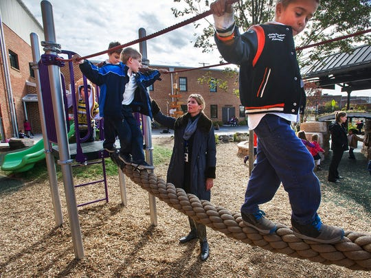From the left, Niles Glasgow, and Aiden Miller come across the rope ladder with the help of kindergarten teacher Liz Gangloff, while Charlie Nugent is in the lead. The playground at York Academy will be available for open play from 6 to 8 p.m. during First Friday April 1.