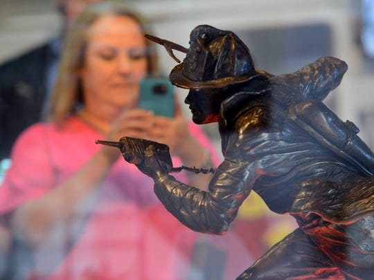 Niki Page takes a photo of a bronze sculpture of FDNY