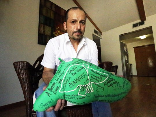 Transplant recipient Armando Martinez shows a pillow shaped like a liver signed and presented to him by the medical staff who assisted him at the University Transplant Center in San Antonio.