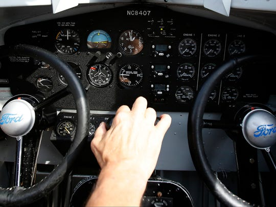 Cody Welch, captain of the 1929 Ford Tri-Motor propeller plane, rests his hand on the throttle Friday after a day of plane rides from the Elmira Corning Regional Airport.