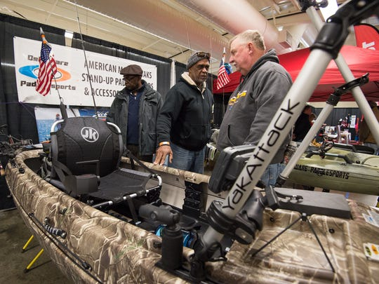 Ernest King, left of Camden, Del., Ahmad Burhani of East Orange, N.J., and Mike Tingle of Laurel, Del., look at a Jackson Kayak that Delaware Paddle Sports had on display at the Delaware State Fair in Harrington.