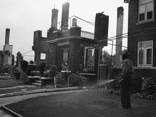 Walter Evans, who lives on Pingree St. on Detroit's West Side, patiently waters his lawn, July 27, 1967 to keep it green in front of his home which was spared from fires set by rioters. Next door are the stark ruins of his neighbor's home burned by a fire that swept almost the whole residential block.
