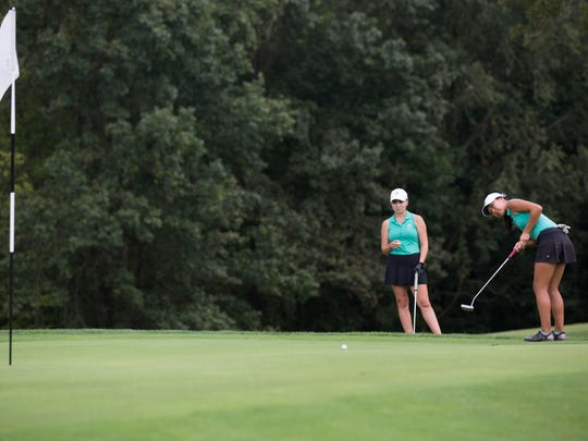 Katelyn Le tries to sink her putt during the girls golf sectionals at Fendrich Golf Course on Saturday afternoon.