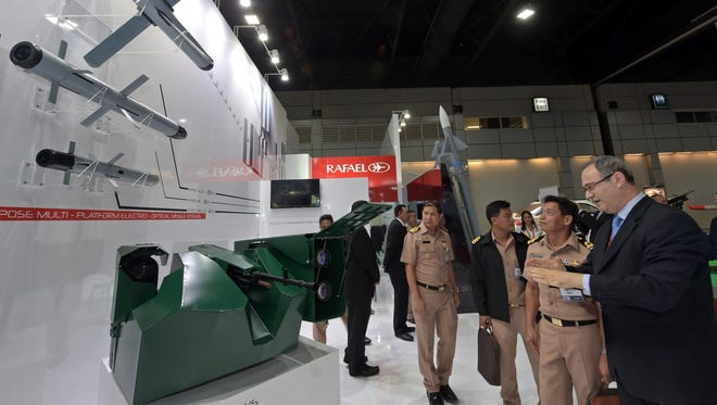 Visitors look at a machine gun platform (bottom) and missiles manufactured by Rafael of Israel during the Defense & Security 2015 exhibition in Bangkok on November 3, 2015.