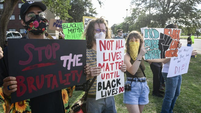 People hold signs protesting police brutality and the death of George Floyd at Tim Cole Memorial Park on Sunday, May 31, 2020, in Lubbock, Texas.