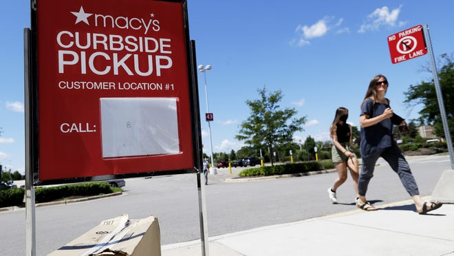 People walk past a curbside pickup sign at Macy's department store in Vernon Hills, Ilinois, in June.