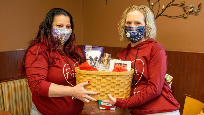 Crystal Lewis, left, and Shawnna Yoka, right, on Monday hold one of many baskets they have put together for community members.