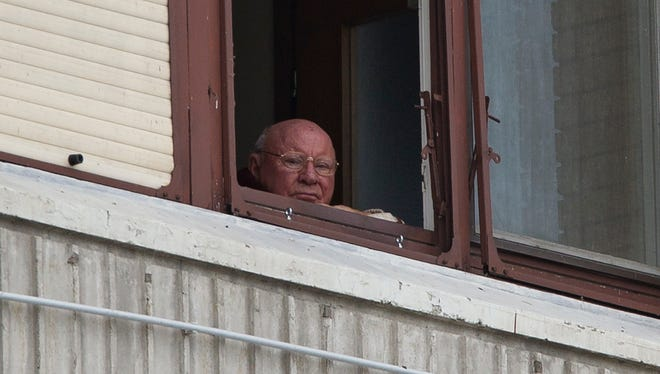 In this July 28, 2014, photo, Jakob Denzinger looks from his apartment window in Osijek, eastern Croatia. Denzinger is among dozens of death camp guards and suspected Nazi war criminals who collected millions of dollars in Social Security payments despite being forced out of the U.S. An Associated Press investigation found dozens of suspected Nazi war criminals and SS guards collected millions of dollars in Social Security payments after being forced out of the United States. (AP Photo/Darko Bandic)