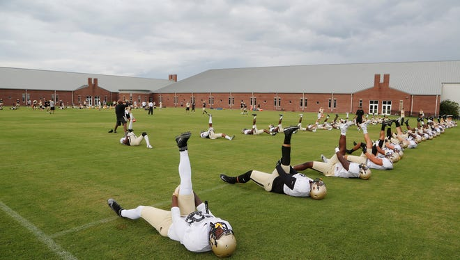 Purdue football players stretch as practice is taken on the road Thursday, August 11, 2016, on the campus of DePauw University in Greencastle.
