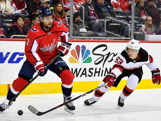 Washington, DC, USA; Washington Capitals defenseman Matt Niskanen (2) looks to pass the puck as New Jersey Devils left wing Jesper Bratt (63) defends during the second period at Capital One Arena on Saturday, Dec. 30, 2017.