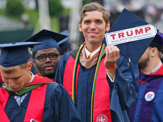 Liberty University graduate, David Westcott Jr. displays a Trump sticker attached to the top of his mortar board as he walks into the stadium with other graduates at the start of commencement ceremonies at the school in Lynchburg, Va. on May 13, 2017.