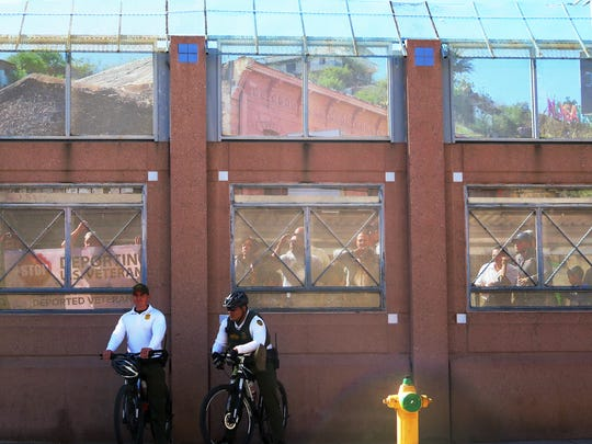A group of people who identified themselves as U.S. military veterans stand in Mexico looking through the border fence as presidential candidate Bernie Sanders made a visit to the border in Nogales, Ariz., Saturday, March 19, 2016. He focused on immigration and said he would fight for immigration reform. (AP Photo/Astrid Galvan)