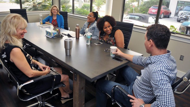 Dr. Mike Ronsisvalle, right, meets with his staff at his new addiction treatment center in Melbourne.