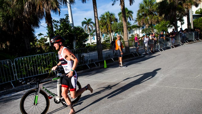 Ross Lenehan, 31, of Cape Coral, transitions from biking to swimming while competing in the 32nd annual Naples Fitness Challenge Triathlon at the Naples Beach Hotel and Golf Club on Sunday, June 3, 2018. Lenehan won the overall sprint competition for the fourth year in a row.