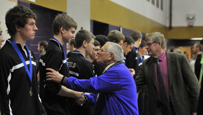 Superintendent Tom Rich congratulates Melrose basketball players at a celebration of the team's state championship.