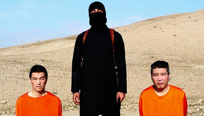This file image taken from an online video released by the Islamic State group's al-Furqan media arm on Tuesday, Jan. 20, 2015, purports to show the group threatening to kill two Japanese hostages.