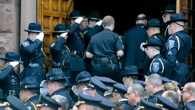 A member of the Ontario County Sheriff's Office caries the remains of deputy Joshua Shaver into St. Mary's Church during the Funeral in Canandaigua. The Ontario County deputy died from injuries in May 12 crash.