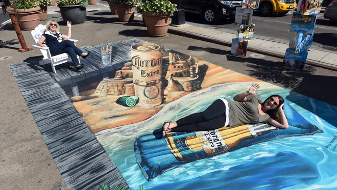 Beth Baynum, left, and Heather Leonhardt, both of New York, count down the 271 days to the start of next summer while lounging in a 250-square-foot, 3D beach scape in the center of New York's Chelsea Triangle on Sept. 23, 2015.
