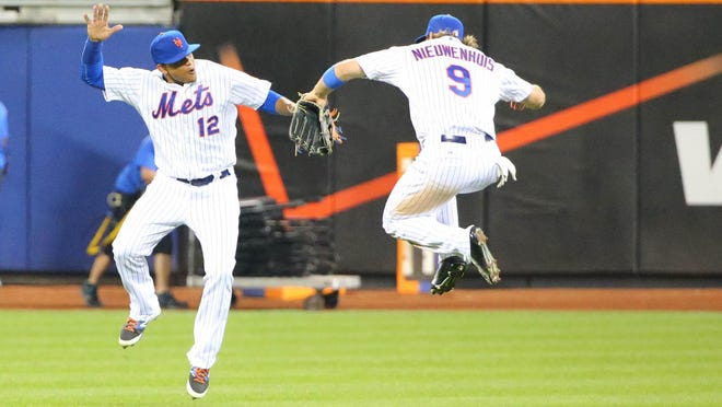 New York Mets center fielder Juan Lagares (12) and left fielder Kirk Nieuwenhuis (9) celebrate the win against the Los Angeles Dodgers at Citi Field. New York Mets won 15-2.