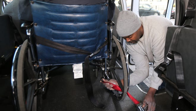 Samora Higgins, right, a driver with RV Ambulette in Yonkers, secures James Gaddy's wheelchair inside the van.