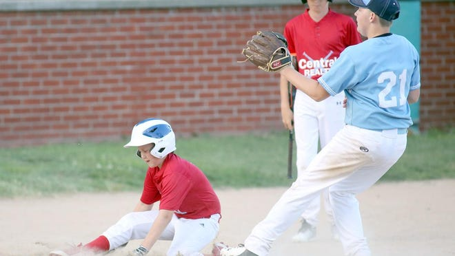 Central Realty's Thad Quint scores while QuinlanAgency.com pitcher Shawn Beach-Reasons prepares to take the throw from the catcher in the fifth inning Tuesday night in Cal Ripken Major at Cooper County Baseball Association ballfield.