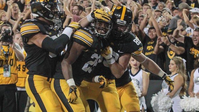 Teammates surround Iowa senior running back Akrum Wadley after Wadley ran in a touchdown against Penn State on Saturday, Sept. 23, 2017, at Kinnick Stadium in Iowa City.