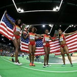 In this photo made with a fish-eye lens, the United States' 4x400-meter women's relay team of (from left) Ashley Spencer, Courtney Okolo, Quanera Hayes, and Natasha Hastings, hold flags after they won the 4x400-meters women's relay during the World Indoor Athletics Championships, Sunday, March 20, 2016, in Portland.