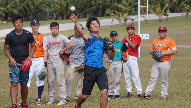 In this Jan. 16, 2016, file photo, members of the Yomiuri Giants work with local baseball players at the Okkodo High School baseball field.
