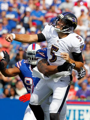 Baltimore Ravens quarterback Joe Flacco (5) gets hit by Buffalo Bills defensive tackle Alan Branch (90) after throwing a pass during the first half at Ralph Wilson Stadium.
