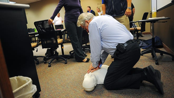 Tom Garry, a real estate broker with Hegg Realtors Inc., performs chest compressions on a CPR manikin during a CPR class Tuesday for real estate brokers with Hegg Realtors Inc. at the Hegg Realtors office on 41st Street in Sioux Falls.