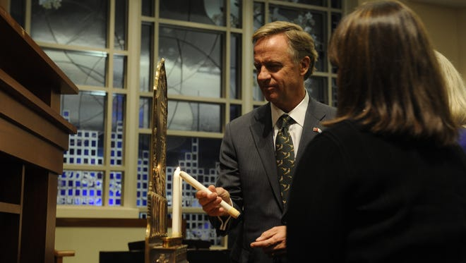 Gov. Bill Haslam lights a candle on the menorah at The Temple on Harding Place Tuesday night.