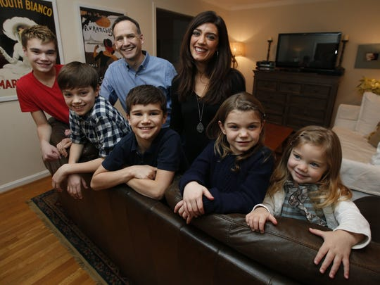 Annie Waters, top right, Matt Waters, and their five children pose in their home in Alexandria, Va. Annie was attending college in Michigan when she met Matt at a bar, and later in church.