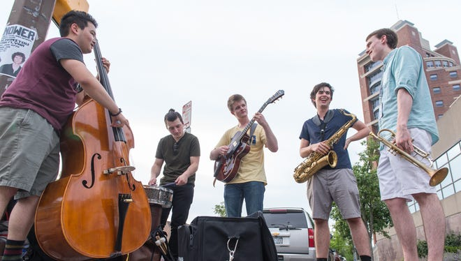 Eastman School of Music students, from left, Mikailo Kasha, Andrew Tachine, Garret Mader, Aiden O'Connor and Nathan Kay set up on Main Street to perform during the festival on June 26, 2016.