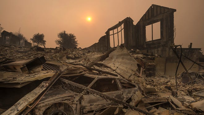 The sun rises through a cloud of smoke after a wildfire swept through the area in Sonoma County  in Santa Rosa, Calif.